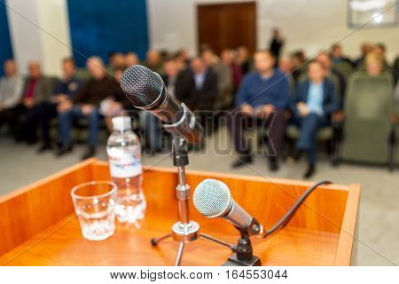 Modern An Acoustic Microphone On The Podium Of The Conference Hall At The Defocused Background Of A