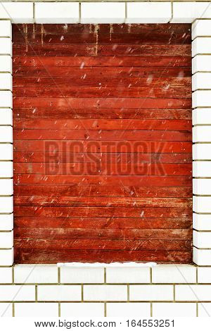 Window In Stone Wall Covered With Wooden Boards In The Winter, It Is Snowing. As An Illustrative Bac
