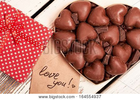 Box of chocolates near card. Gift box with star pattern. Recipe of good mood.