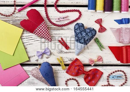 Colorful bow ties on table. Fabric hearts and blank papers. The workspace of a true artist.