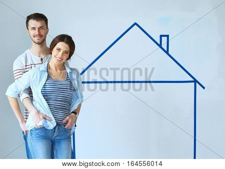 Couple sitting in front of painted home on wall.