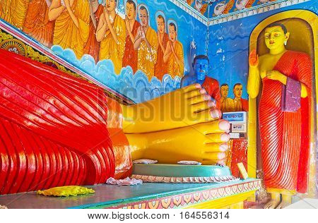 ANURADHAPURA SRI LANKA - NOVEMBER 26 2016: The legs of Reclining Buddha statue Blue Buddha in corner known as statue of of Medicine or Healing and Standing Buddha statue in Isurumuniya Rock Temple on November 11 in Anuradhapura.