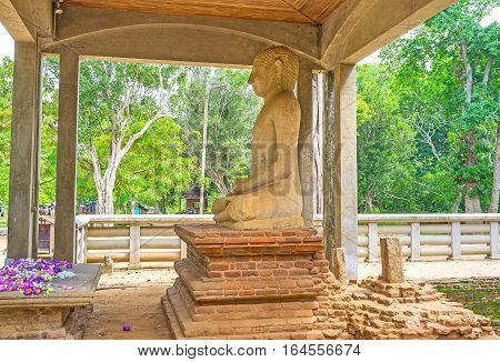 The Samadhi Buddha Statue in pose of meditation is the place of veneration surrounded by ancient ruins and greenery of Mahamevnawa Park Anuradhapura Sri Lanka.