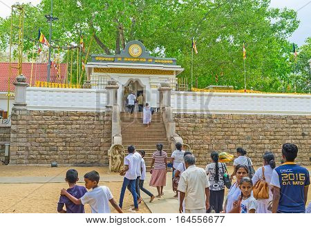 ANURADHAPURA SRI LANKA - NOVEMBER 26 2016: The pilgrims visit Bodhi Tree Temple one of the most sacred relics of the Buddhism on November 26 in Anuradhapura.