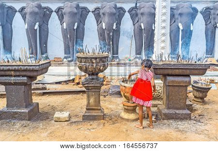 The little girl puts the ritual incense sticks to the stone bowl at the wall of Ruwanwelisaya complex decorated with plaster elephants Anuradhapura Sri Lanka.
