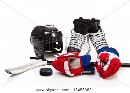 Ice hockey equipment featuring safety helmet pair of skates gloves stick and a hockey puck. Isolated on white background.