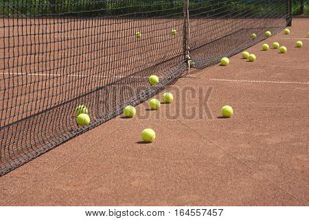 Ground court with net and many yellow tennis balls in summer day