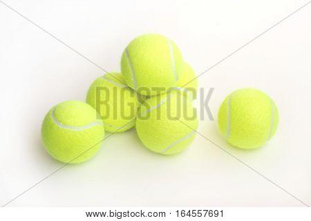 Yellow tennis balls indoor on white background closeup