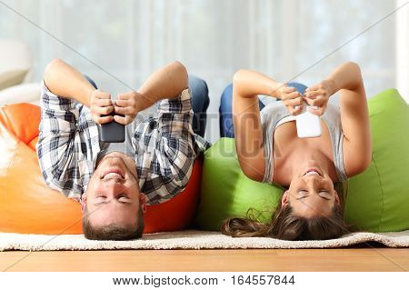 Funny roommates upside down online with their smart phones lying on orange and green poufs in the living room at home