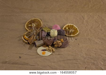 Composition of chocolate candies and dried oranges on a crumpled paper. sweets lie on paper