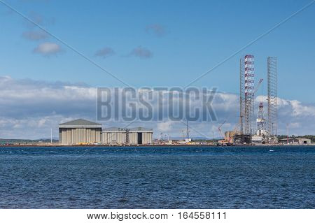 Balnapaling Scotland - June 3 2012: Wide overview of Galaxi Z petroleum and national gas drill platform under construction in the harbor. Tall frames and cranes. Heavy metal contraption. North Sea in front under blue cloudy sky.