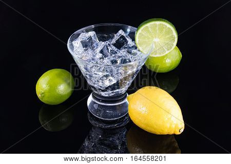 Sparkling Beverage In A Martini Glass With Lemons And Limes On A Black Background
