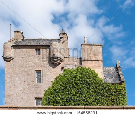 Dornoch Scotland - June 3 2012: Side view of beige-brown castle facade with gray roofs behind green tree and under blue sky with a few white clouds. Building was restored and features windows and lookouts.