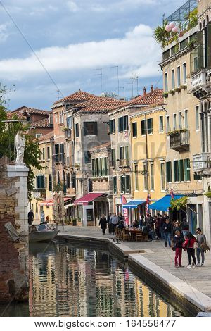 VENICE, ITALY - OCTOBER 8: People talking and walking along characteristic venetian canal  OCTOBER 8, 2016 in Venice, Italy