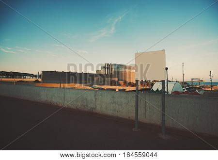 Mock up of empty white billboard near seaside and industrial zone low concrete fence behind sunset with clear teal sky with spindrift clouds Barcelona Spain