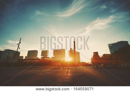 Wide angle shot of dramatic sunset with flare and godrays near in Barcelona Forum district with distant residential houses and square with people clear sky and spindrift clouds Spain