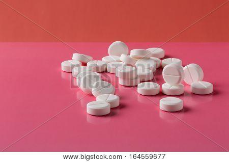 Heap of white round pills on pink background
