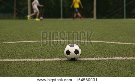 Classic ball for playing soccer in white with black accents on artificial turf against two football players, close-up view