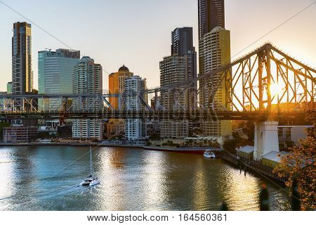 Yacht passing under Brisbane Story Bridge as the sunsets behind the cityscape
