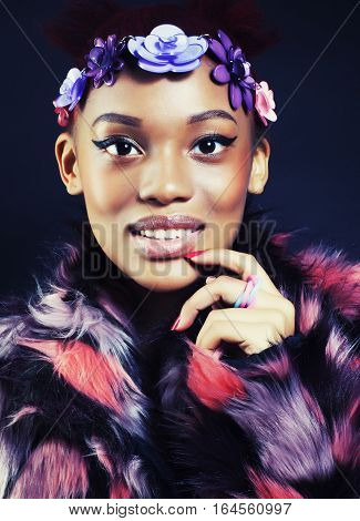 young pretty african american woman in spotted fur coat and flowers jewelry on head smiling sweet etnic girl close up