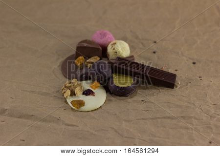 Composition of chocolate candies and dried oranges on a crumpled paper. focus on near objects. sweets lie on paper