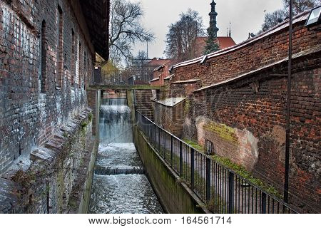 Restless waters Radunia Channel in the place of the former ancient water wheels. Inner of the medieval Great Mill in the Gdansk Poland. The Mill was built by the Teutonic Knights in 1350.