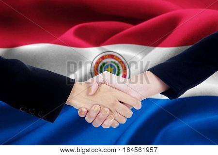 Image of agreement handshake with two worker hands shaking hands in front of a national flag of Paraguay
