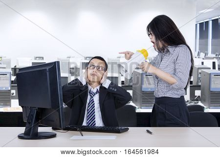 Image of an angry female employee shouting at her manager through megaphone while working with a computer in the workplace