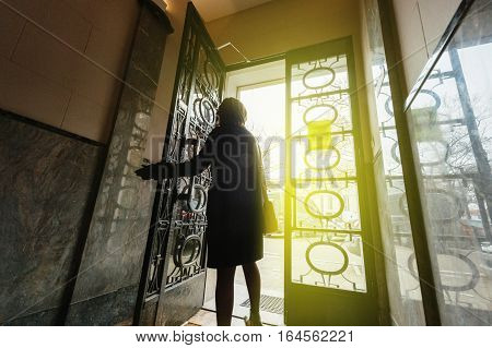 Elegant woman wearing French coat walking out the door of a luxury French building - concept for business success new beginnings and personal success