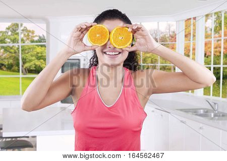 Attractive young woman holding two pieces of orange fruit in front of her eyes shot in the kitchen