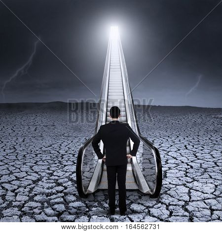 Young businessman standing by the escalator on dried land with bad weather