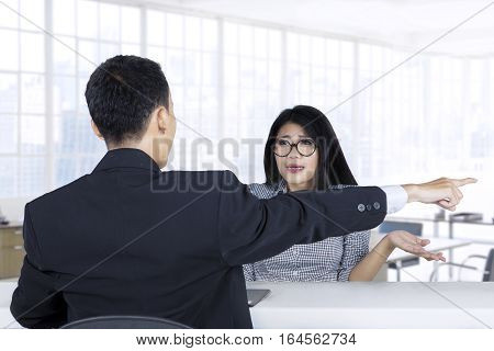 Rear view of a businessman expelling a female worker by pointing out in the office