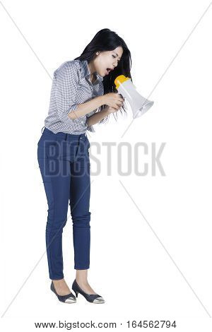 Full length of young businesswoman shouting through a megaphone while looking at down in the studio
