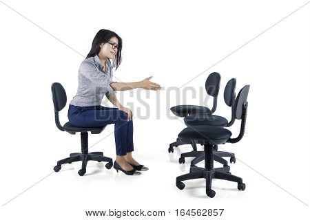 Image of beautiful business woman sits on a chair and stretches out her hand to shake hands with empty chairs in the studio