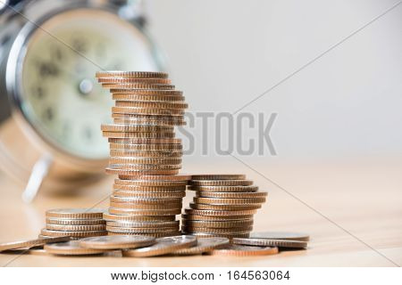 Concept business finance save money Coins stack on wood table with blurred alarm clock background