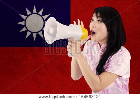 Portrait of happy Chinese girl wearing cheongsam dress and using a megaphone to congratulate Chinese new year with flag of Taiwan