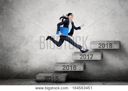 Picture of female entrepreneur running on the stairs toward number 2018 while carrying a folder