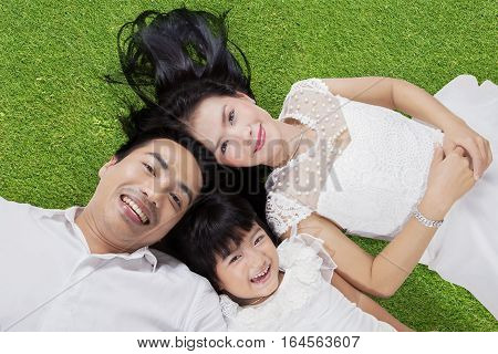 Unique perspective of happy Asian family smiling at the camera while lying down on the green grass at field