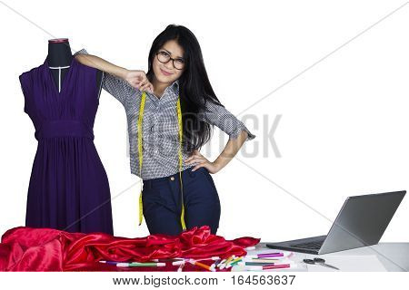 Portrait of a beautiful fashion designer smiling at the camera while leaning on a mannequin isolated on white background
