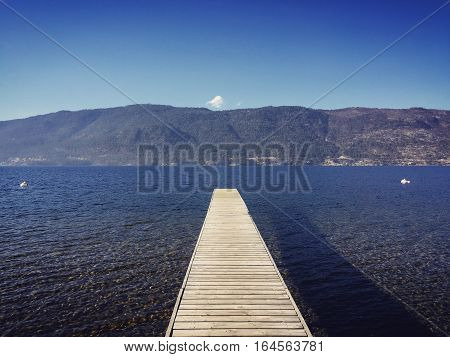 Wooden pier on lake.  Scenic lake landscape with pier in foreground.  Mountains and clear blue sky with one isolated small white cloud in background.