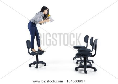 Image of angry female manager standing on a chair and shouting with a megaphone while looking down with empty chairs