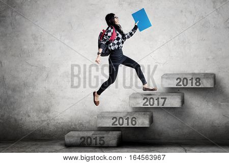 Picture of female student running on the stairs toward number 2018 while carrying a folder