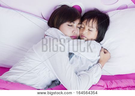 Portrait of beautiful mother and cute child sleeping together on the bed