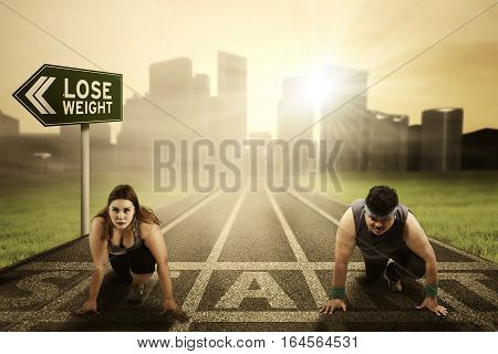 Image of overweight people kneels on the start line while ready to compete and try to chase their dream with text of losing weight on the road sign