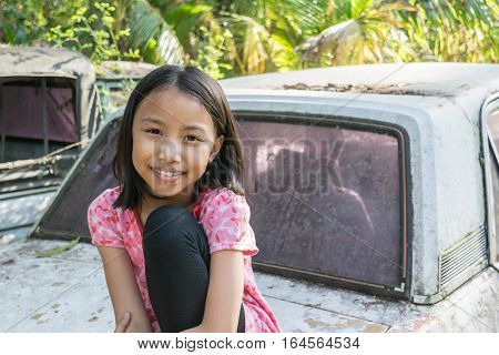 Close Up Happy Adorable Asian Kids. Portrait Of Happy Joyful Smiling Kids Sitting On The Old Car.