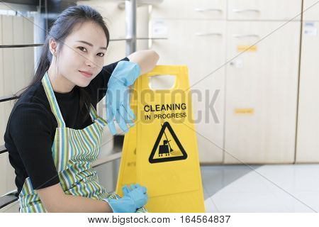 Housekeeping or maid taking a break while working leaning a cleaning sign board