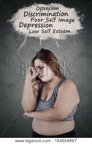Blonde woman with overweight body wearing sportswear and looks frustrated thinking her problems