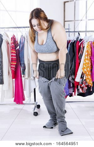 Picture of overweight woman tries to wear her old jeans with clothes rack in the bedroom