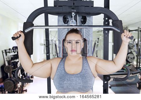 Portrait of serious obese female exercising and flexing muscles on a cable machine in the fitness center