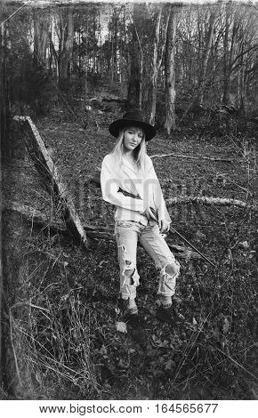 Young blond woman standing in the woods with a gun